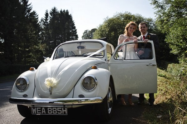 bride and groom in white VW beatle