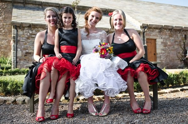 bride in a Candy Anthony dress and bridesmaids in black dresses