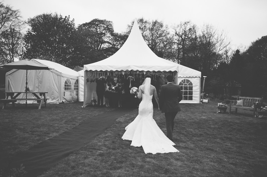 bride and groom going into the wedding marquee