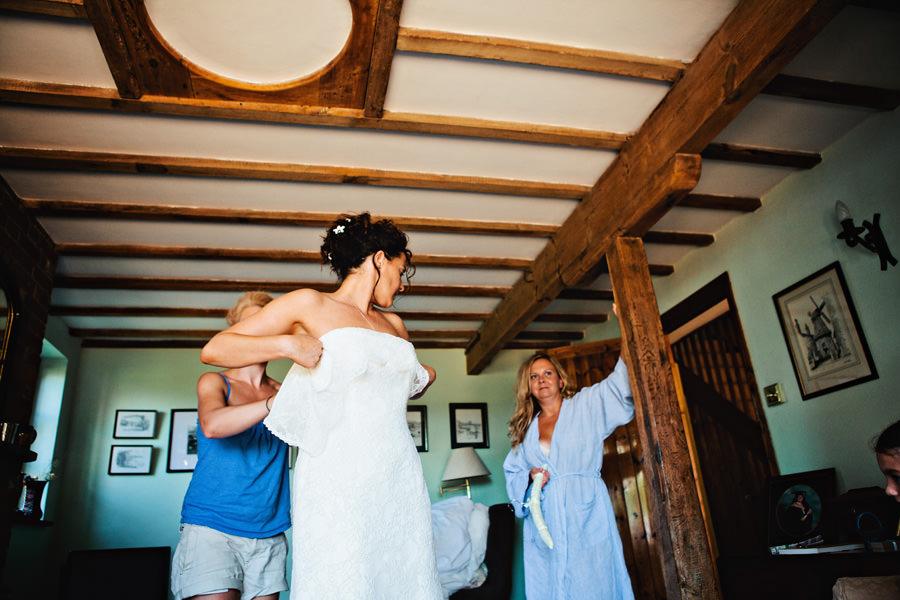 bride putting on Augusta Jones wedding dress