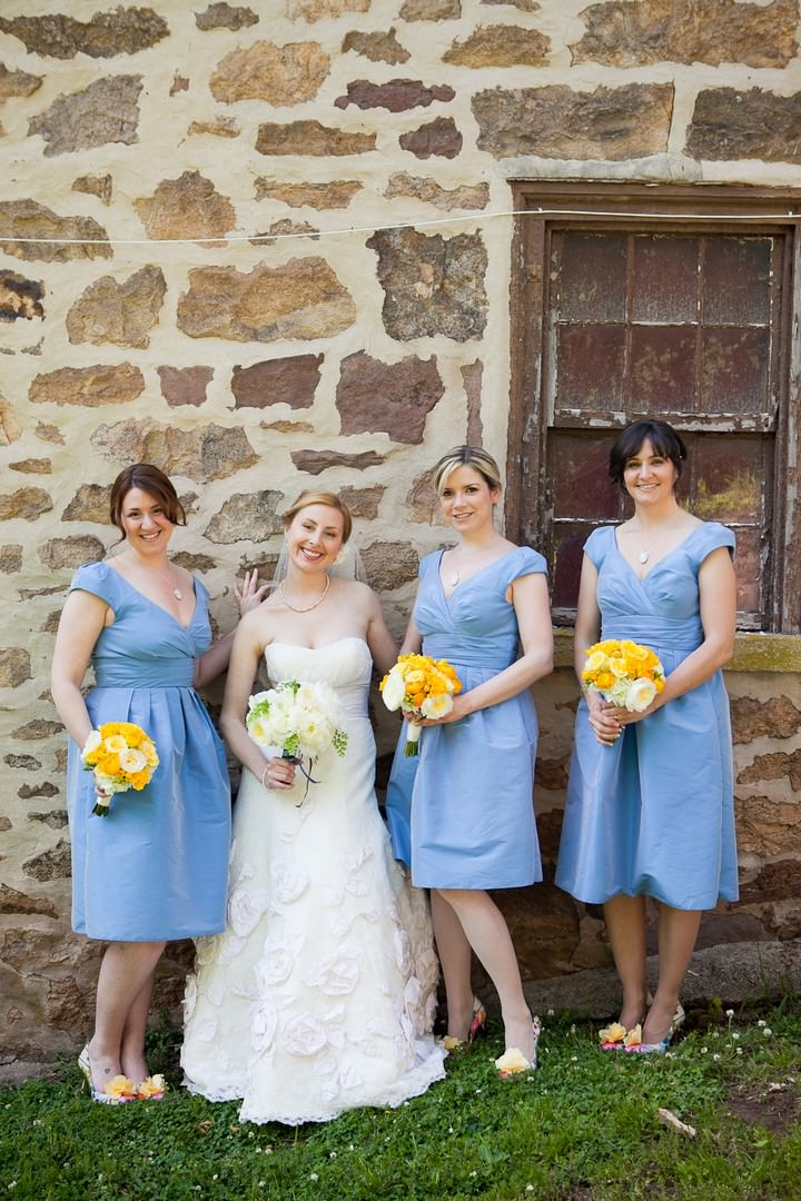 bride with bridesmaids in blue dresses and yellow flowers