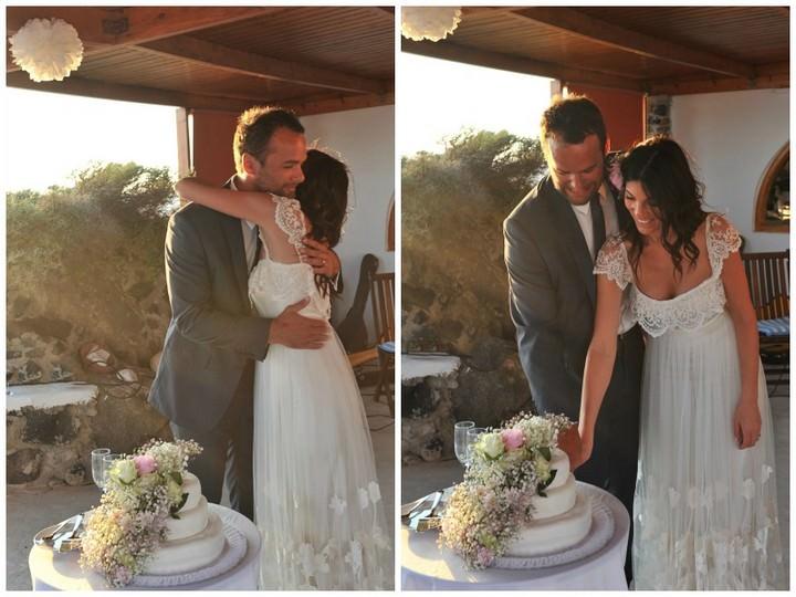 couple cutting wedding cake in Santorini