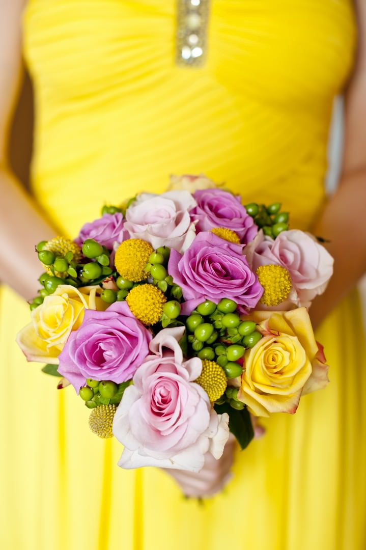yellow bridesmaid holding bouquet