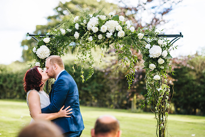 Louise and Sam's Gold and White Outdoors Wedding with an Evening Pool Party first kiss
